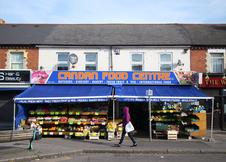 ethnic food: Reading,England - March 6, 2015: A pedestrian passes by an ethnic food supermarket in Reading, England where ethnic peoples can buy Halal meat and International Food alongside traditional groceries.