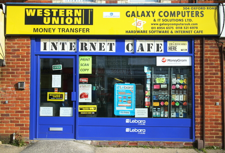 western town: Reading,England - March 6, 2015: Computer hardware and software business in Reading, England providing an Internet Cafe, Western Union money transfers and mobile phone services in the High Street.