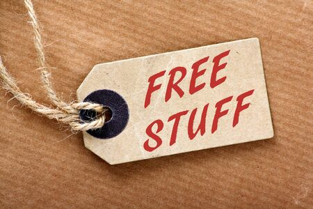 enticement: The phrase Free Stuff on a brown paper luggage tag on a brown wrapping paper background Stock Photo