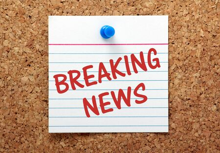 news current events: The phrase Breaking News on a lined index card pinned to a cork bulletin board Stock Photo
