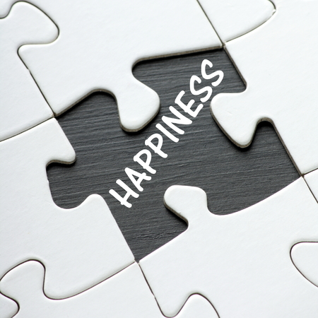 The word Happiness on a blackboard revealed by a missing jigsaw puzzle piece Stock Photo