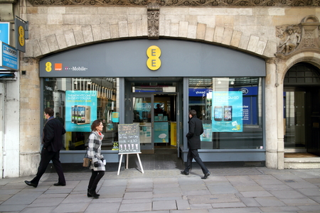 ee: London, United Kingdom - April 02, 2015: People passing by and entering an EE store in London, England. The EE company delivers mobile and fixed communications services in the UK and includes the Orange and T-Mobile companies Editorial