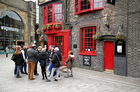 typically english: London, United Kingdom - April 02, 2015: A tour group of people and their guide form a huddle outside The Anchor Pub in Southwark, London. Editorial