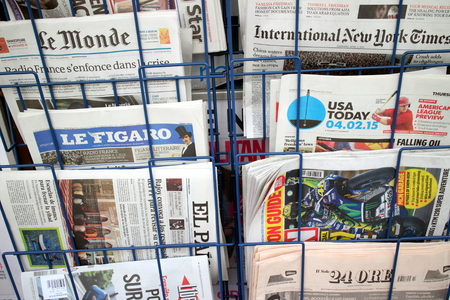 broadsheet: London, United Kingdom - April 02, 2015: International and Foreign Language newspapers on display in a rack outside a store. Editorial
