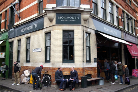 retailing: London, England - April 02, 2015: People outside and queuing to enter the Monmouth Coffee Company store near Borough Market, London. The company began roasting and retailing coffee in London in 1978