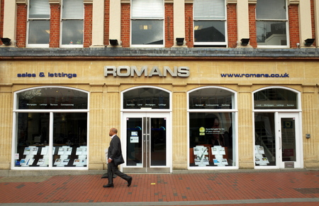 Reading, England - April 23, 2015: A man walks by a Romans Estate Agents window display in Reading, England. According to the Nationwide Building Society, house prices rose over 7% in the UK in 2014