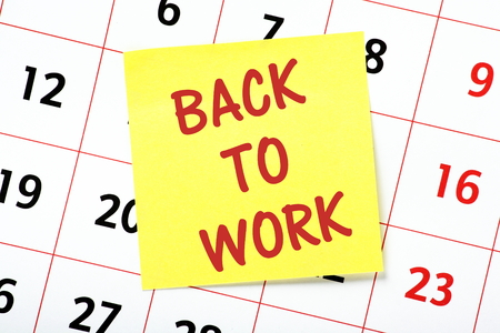 back to work: The phrase Back To Work on a yellow sticky note attached to a wall calendar as a reminder