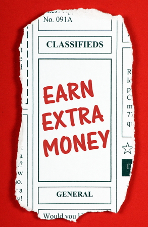earn money: The phrase Earn Extra Money in red text on a newspaper clipping from the classified advertising section Stock Photo