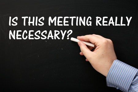 necessary: Male hand wearing a business shirt writing the question Is This Meeting Really Necessary on a blackboard.