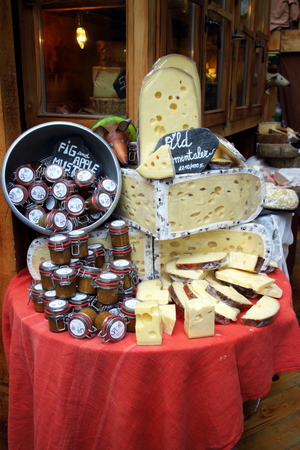 traded: London, England - April 02, 2015: A display of Emmental cheese rounds and jars of sauce on a stall in Borough Market, London. The market has traded in Southwark, London for more than 250 years