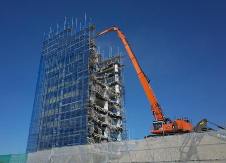 demolition: Bracknell, England - April 14, 2015: A demolition crane goes to work on a multi story office block in Bracknell, England