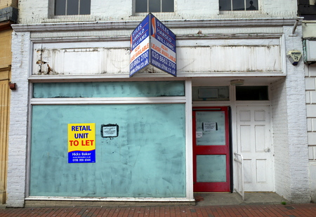 urban decline: Reading, England - April 23, 2015: Empty retail unit with a real estate sign in Reading, England. In 2014 one in three high street properties in Britain were empty according to The Local Data Company
