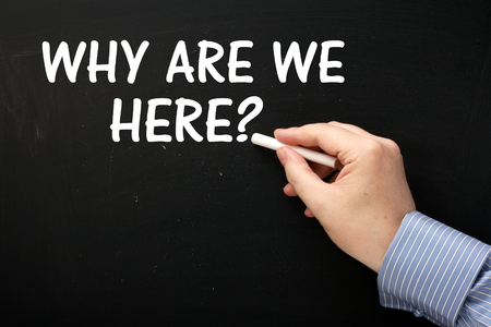 Male hand writing the question Why Are We Here? on a blackboard in white text photo