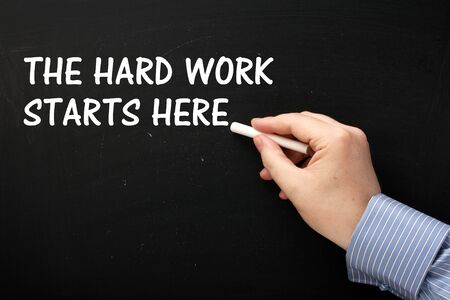 self improvement: Male hand wearing a business shirt writing the phrase The Hard Work Starts Here on a blackboard in white text