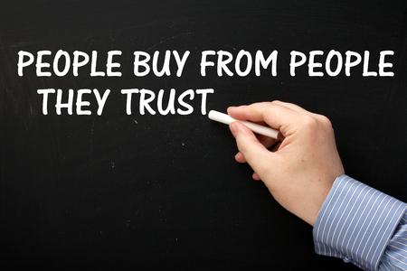 黒板に人々 を購入からの人々 彼らは信頼白色のテキストでフレーズを書くビジネス シャツを着ている男性の手