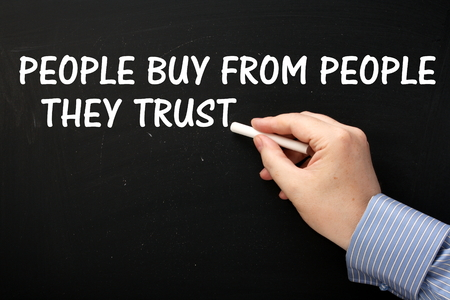 Male hand wearing a business shirt writing the phrase People Buy From People They Trust in white text on a blackboard