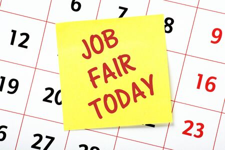 The phrase Job Fair Today on a yellow sticky note attached to a wall calendar as a reminder Banque d'images