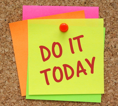 The phrase Do It Today on a yellow sticky note pinned to a cork notice board as a reminder photo