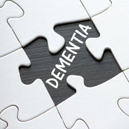 aging brain: The word DEMENTIA on a blackboard revealed by a missing jigsaw puzzle piece Stock Photo