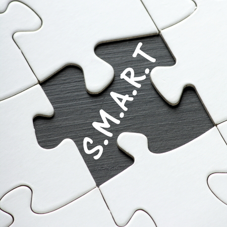 attainable: The word SMART revealed by a missing jigsaw puzzle piece. SMART is the business planning acronym for SpecificMeasurable Attainable Relevant and Timely Stock Photo