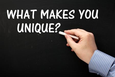competitividad: Mano masculina que lleva una camisa de negocios por escrito la pregunta �Qu� te hace �nico en una pizarra en el texto blanco