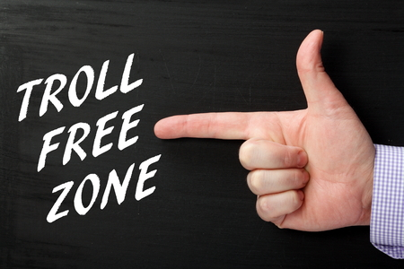 acceptable: Male hand pointing finger gesture at the phrase Troll Free Zone in white text on a blackboard