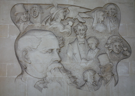 dickens: London England  April 30 2015: Stone mural of Charles Dickens and some of his characters on the outside of a building constructed over one of his former homes in Devonshire Terrace London Editorial