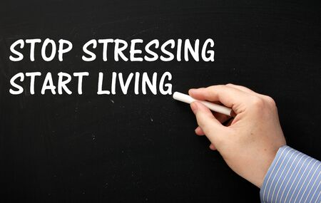 stressing: Male hand wearing a business shirt writing the phrase Stop Stressing Start Living in white text on a blackboard