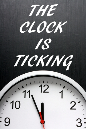 The Clock is Ticking written on a blackboard with a clock face