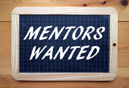 mentors: The phrase Mentors Wanted in white text on a slate blackboard Stock Photo