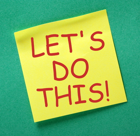 posted: The phrase Lets Do This in red text on a yellow sticky note posted on a green notice board