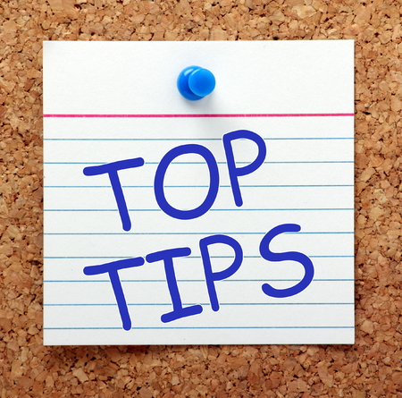 The phrase Top Tips in blue text on an index card pinned to a cork notice board as a reminder