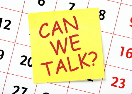 posted: The question Can We Talk in red text on a yellow sticky note posted on a calendar page as a reminder Stock Photo