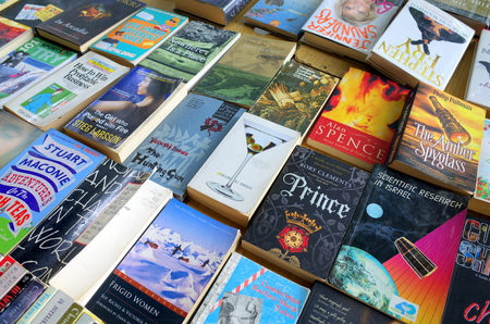 in a row: London, England - August 20, 2015: A variety of paperback books on display and for sale at a market in Central London
