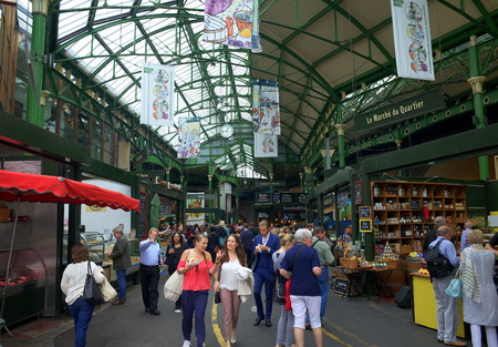 traded: London, England - August 20, 2015: Visitors and shoppers in the covered section of Borough Market in London, England. The market has traded in Southwark, London for more than 250 years