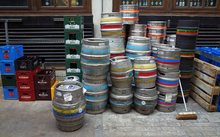 kegs: London, England - Sept 09, 2015: Delivery of beer in metal kegs and plastic crates stacked on the pavement at the rear of a public house in London, England.
