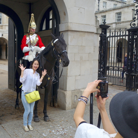 cavalry: London, England - August 20, 2015: People posing for and taking photographs in front of a  Household Cavalry soldier on horseback at the entrance of the Horse Guards building in London, England Editorial