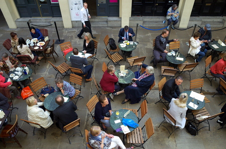 visitors area: London, England - Sept 09, 2015: People seated at tables provided by a cafe in the indoor area of Covent Garden in London, England. The area receives over 40 million visitors a year Editorial
