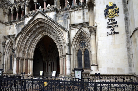 London, England - Sept 09, 2015: Exterior facade of the Royal Courts of Justice in London, England showing the coat of arms of the courts and the archway of the main entrance Editorial