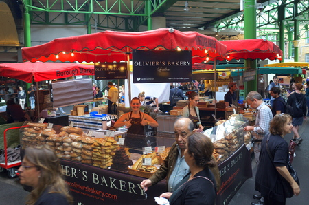 London, England - August 20, 2015: People walk by whilst someone is being served by staff at a bakery stall in Borough Market, London. A market has traded in Southwark, London for more than 250 years