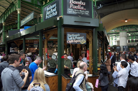 traded: London, England - August 20, 2015: Staff can be seen working as people surround a seafood stall in Borough Market, London. The market has traded in Southwark, London for more than 250 years