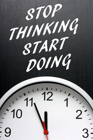 time out: The phrase Stop Thinking Start Doing in white text on a blackboard above a clock with the hands pointing towards twelve or midnight