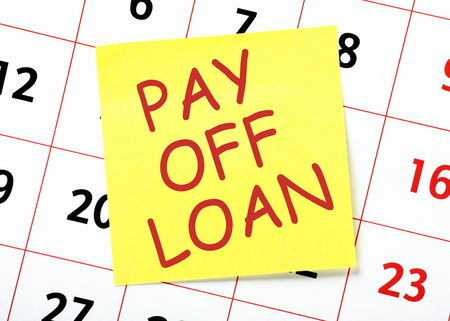 payday: Pay Off Loan message in red text on a yellow sticky note posted on a wall calendar as a reminder Stock Photo