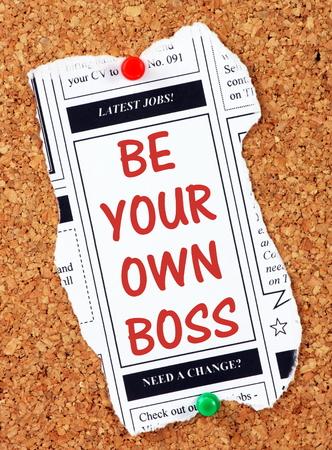 patron: Sea su propio jefe en texto rojo sobre un recorte de la sección de anuncios clasificados de un periódico, clavado en un tablón de corcho como un recordatorio para iniciar su propio negocio Foto de archivo
