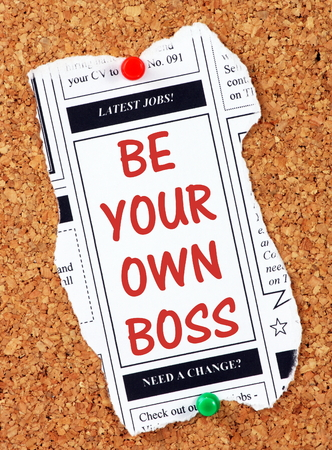 Be Your Own Boss in red text on a clipping from the classified advertising section of a newspaper, pinned to a cork notice board as a reminder to start your own business