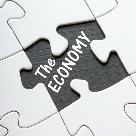 slump: The phrase The Economy in white text on a blackboard as revealed by a missing jigsaw puzzle piece Stock Photo