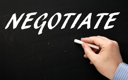 negotiate: Hand writing the word Negotiate in white text on a blackboard using a chalk stick Stock Photo