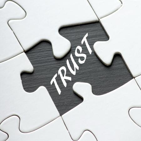 piezas de rompecabezas: La palabra confianza en el texto blanco en una pizarra según lo revelado por una pieza de rompecabezas faltante
