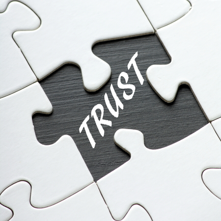 puzzle pieces: The word Trust in white text on a blackboard as revealed by a missing jigsaw puzzle piece