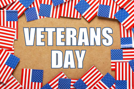 white day: The phrase Veterans Day in block letters on a paper background surrounded by a border of flags of the United States of America